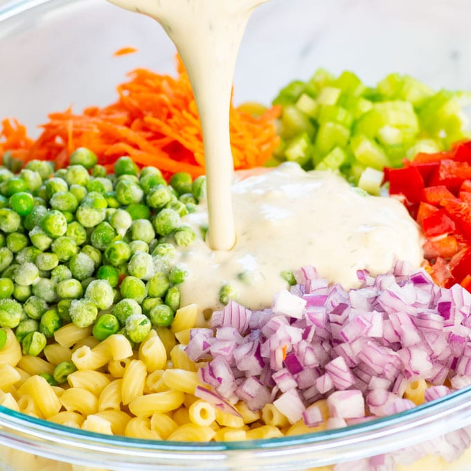 dressing being poured over macaroni salad