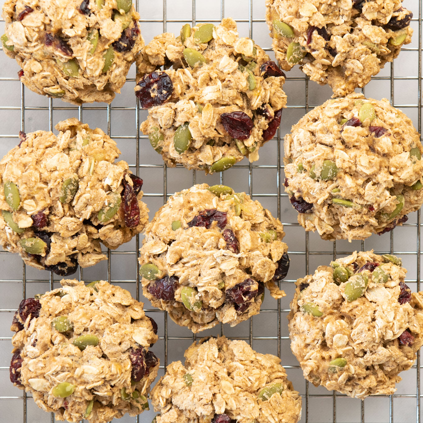 closeup of oatmeal cookies with fruit and nuts on a cooling rack