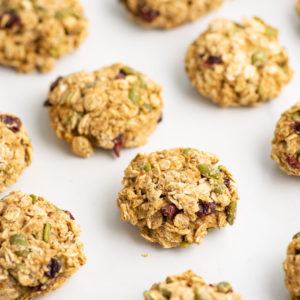 breakfast cookies with dried cranberries and pepitas on white background