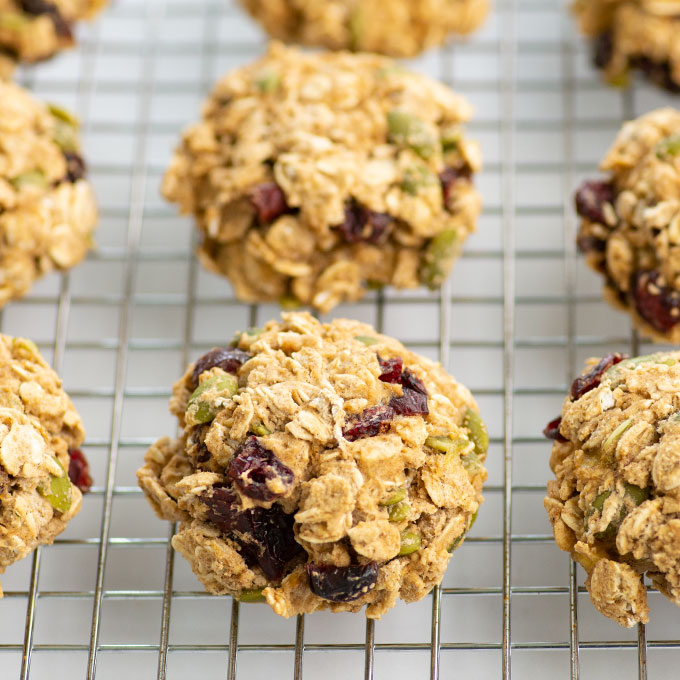 oatmeal cookies with dried cranberries and pepitas on a cooling rack