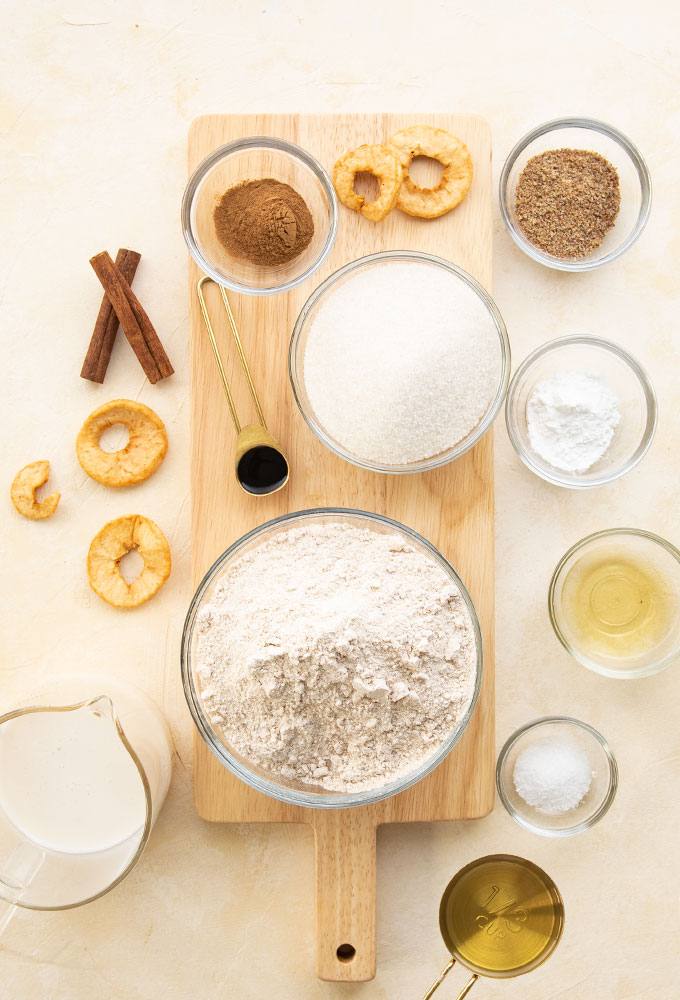 ingredients for vegan apple muffins on light pink background