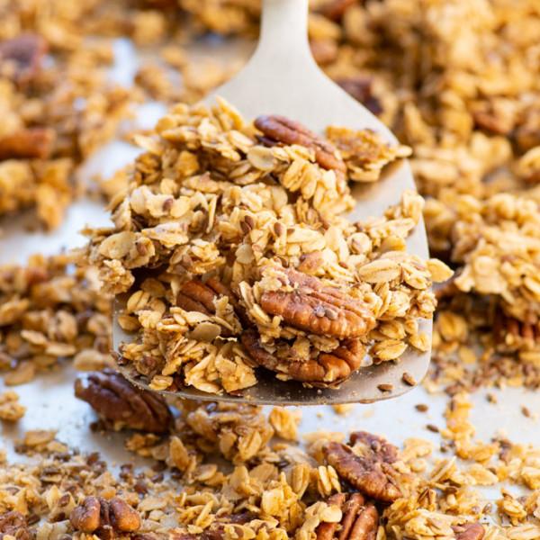 homemade vegan granola on a spatula over a baking sheet