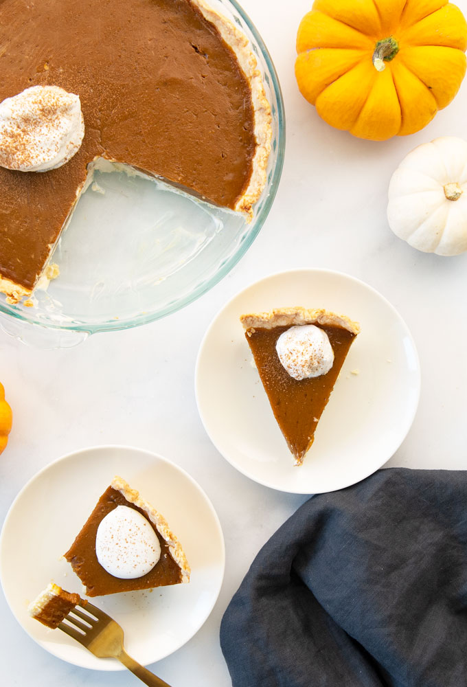 slices of vegan pumpkin pie on plates with a full pie in a pie pan