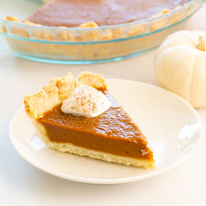 slice of pumpkin pie on a plate with whipped cream