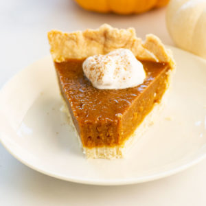 slice of pumpkin pie on a plate with a bite taken out
