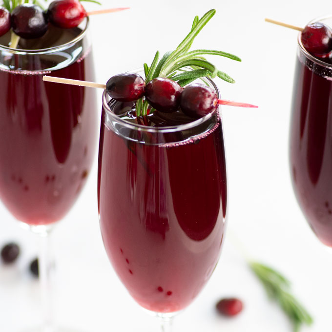 mimosas garnished with fresh cranberries and rosemary