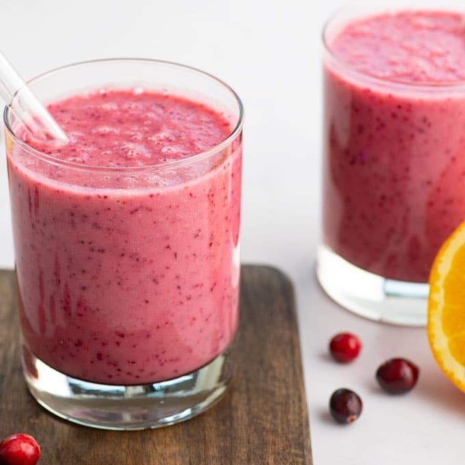 two vegan cranberry smoothies with berries and oranges