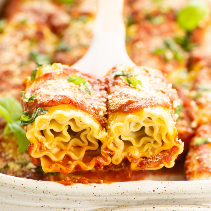two vegan lasagna roll ups with marinara sauce and basil