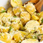 closeup of vegan potato salad in mixing bowl with fresh rosemary and cracked black pepper