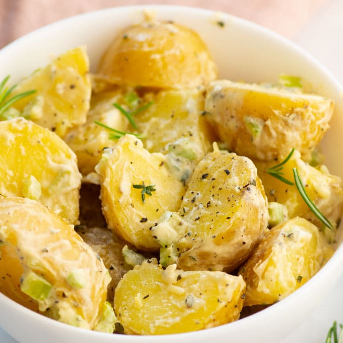 vegan potato salad in a bowl with fresh thyme and rosemary