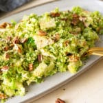shaved brussel sprout salad topped with pecans and apples