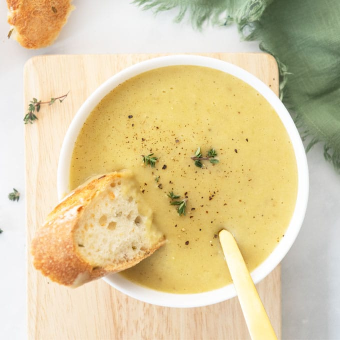bowl of leek and potato soup with piece of bread