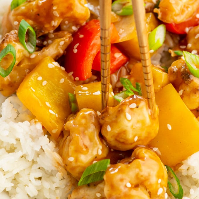 oven fried cauliflower with veggies and sweet and sour sauce over rice