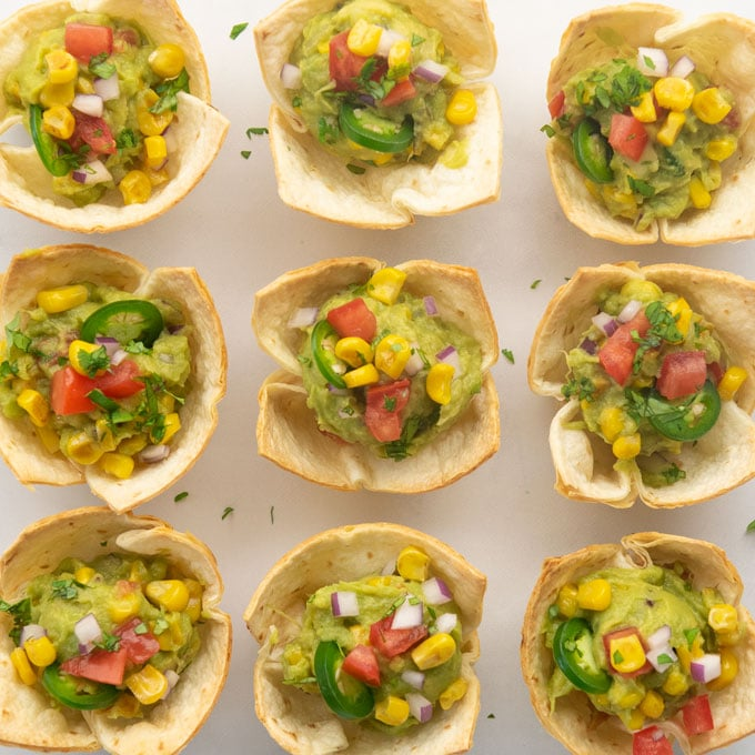 overhead view of guacamole cups garnished with tomato, onion, corn, jalapeno, and cilantro