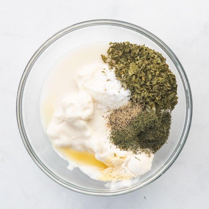 bowl with herbs, mayo, almond milk, lemon juice