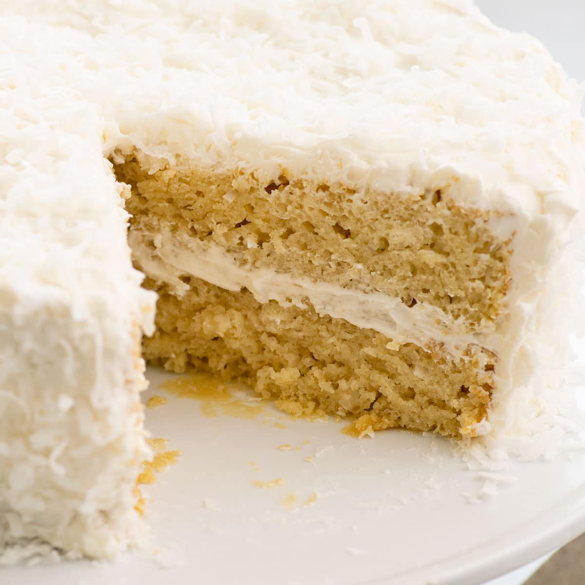 close up of coconut cake with slice taken out