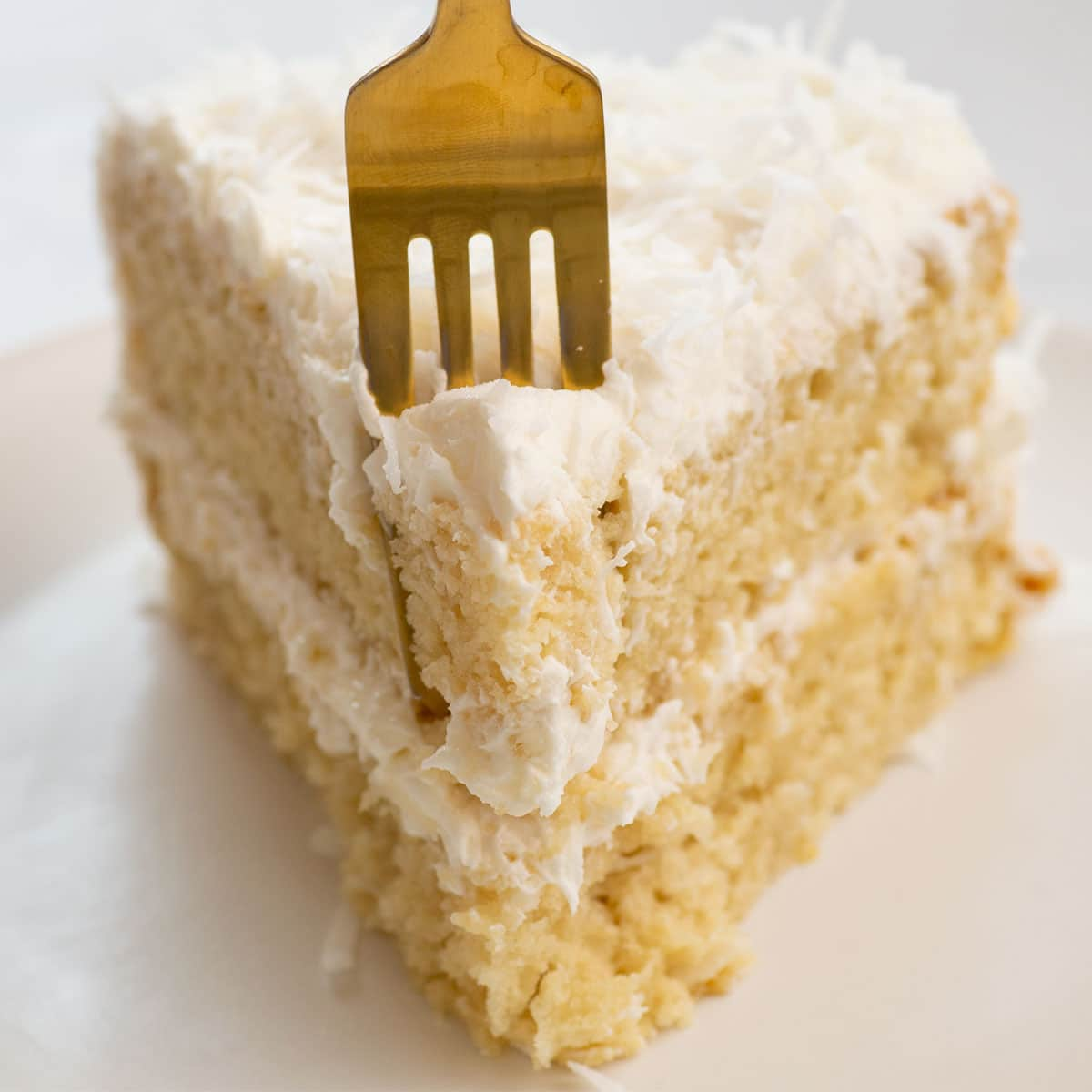 fork going into a slice of coconut cake