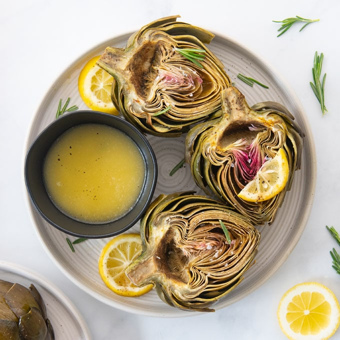 plate of oven baked artichokes with lemon and plant-based garlic butter