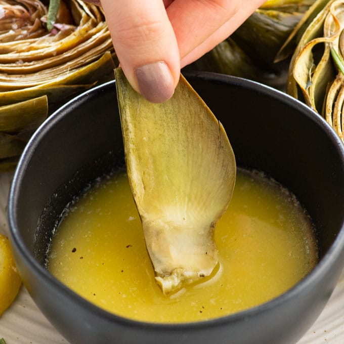dipping roasted artichokes with vegan garlic butter