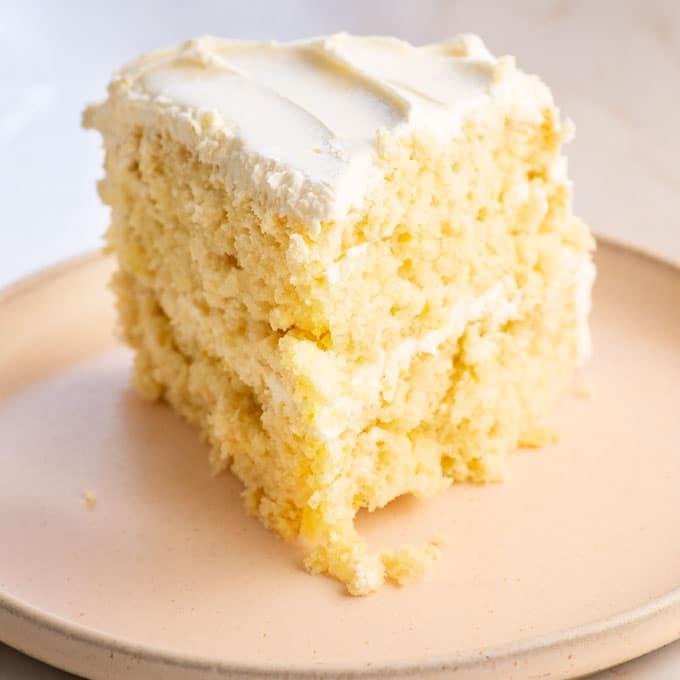 slice of vegan lemon cake on light pink plate