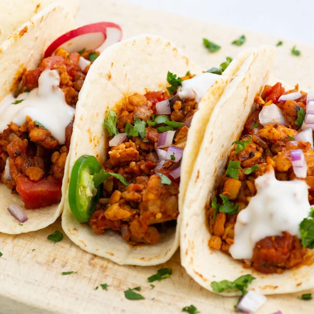 vegan tempeh tacos with crema, onion, jalapenos, cilantro