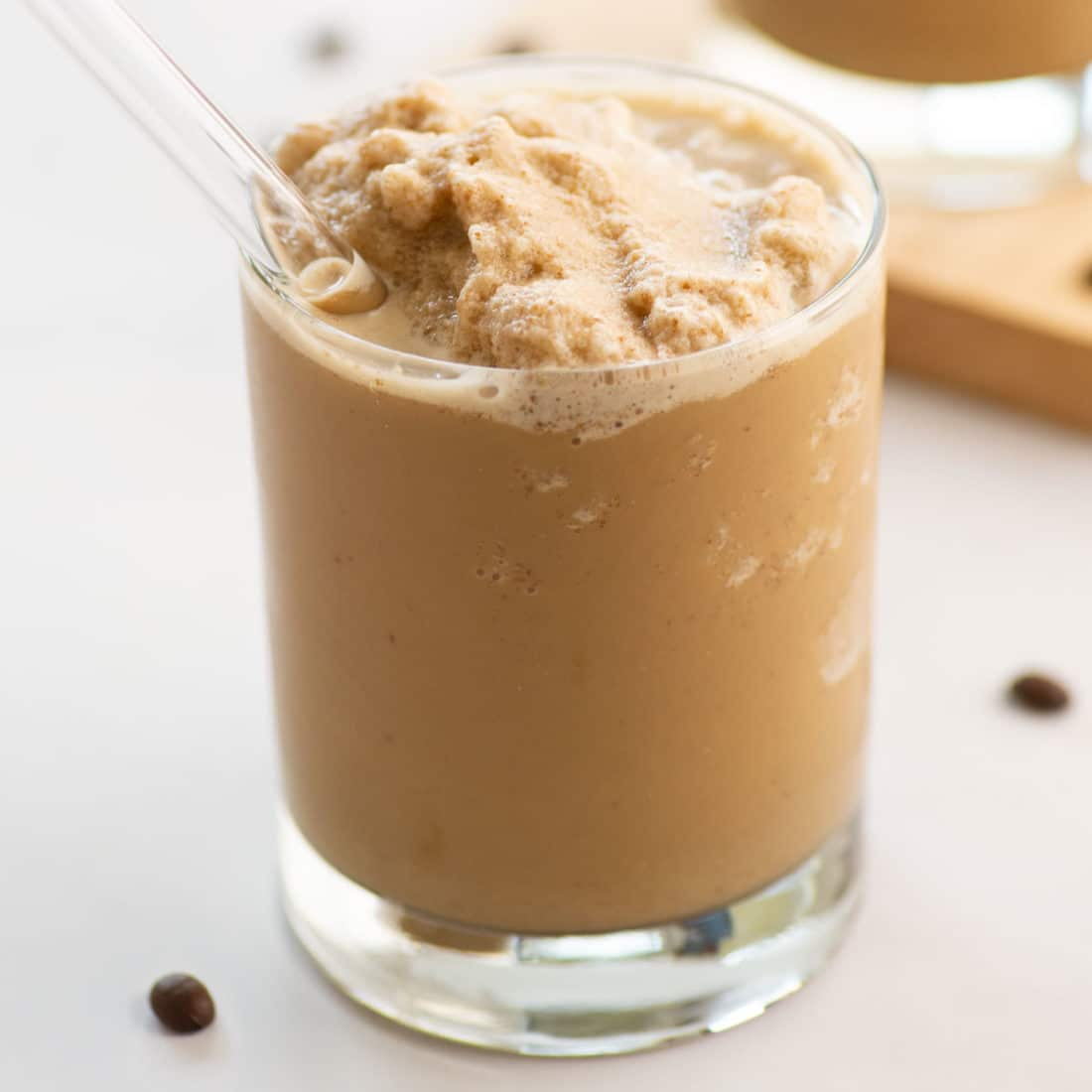 close up vegan coffee smoothie with glass straw