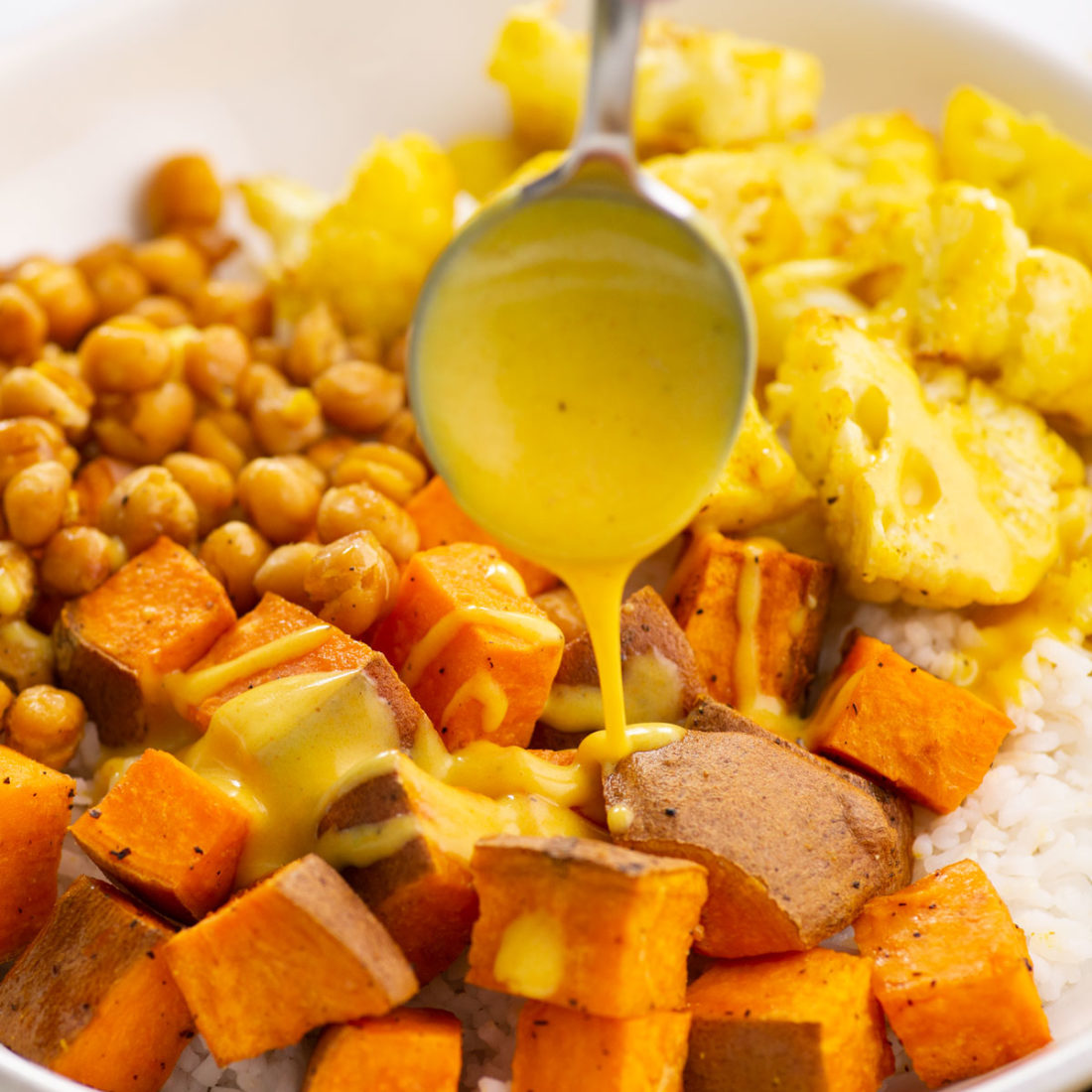 pouring sunshine sauce onto a rice bowl with sweet potatoes, cauliflower, and chickpeas