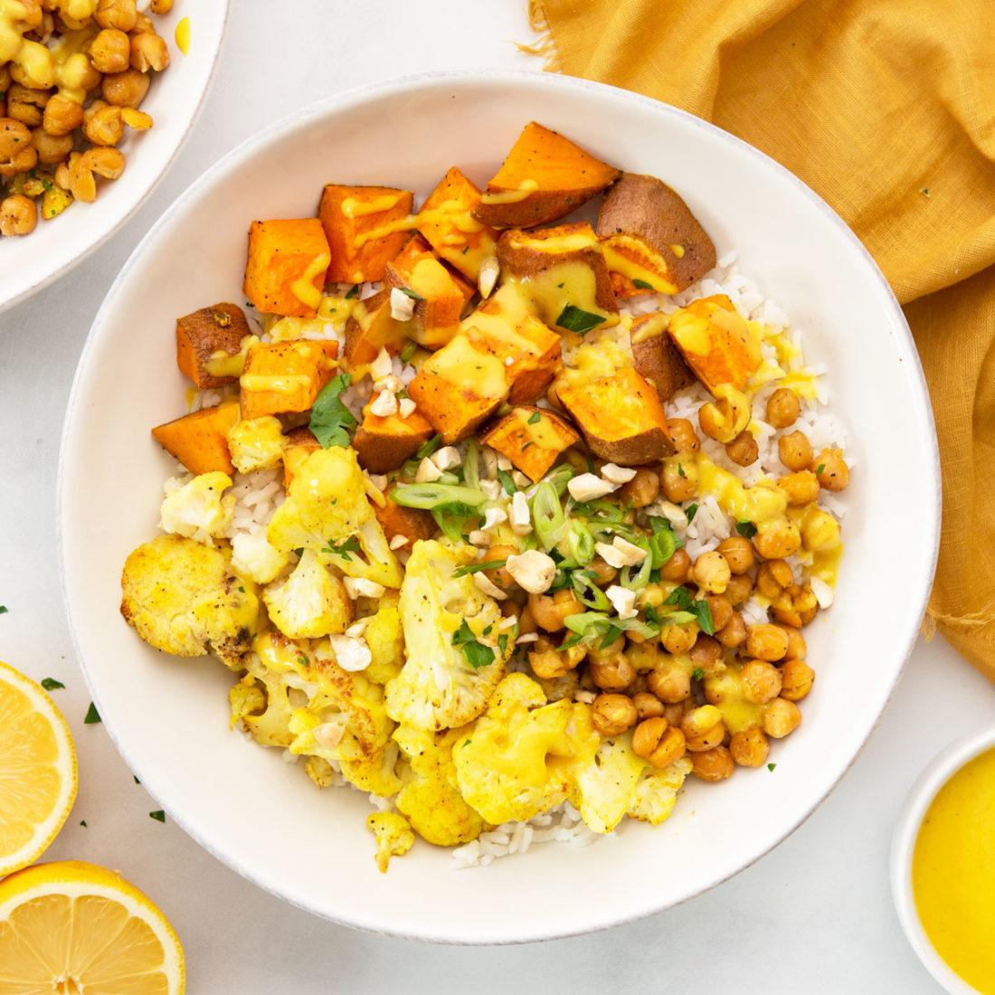 a bowl layered with rice, chickpeas, sweet potatoes, cauliflower, and lemon turmeric sauce