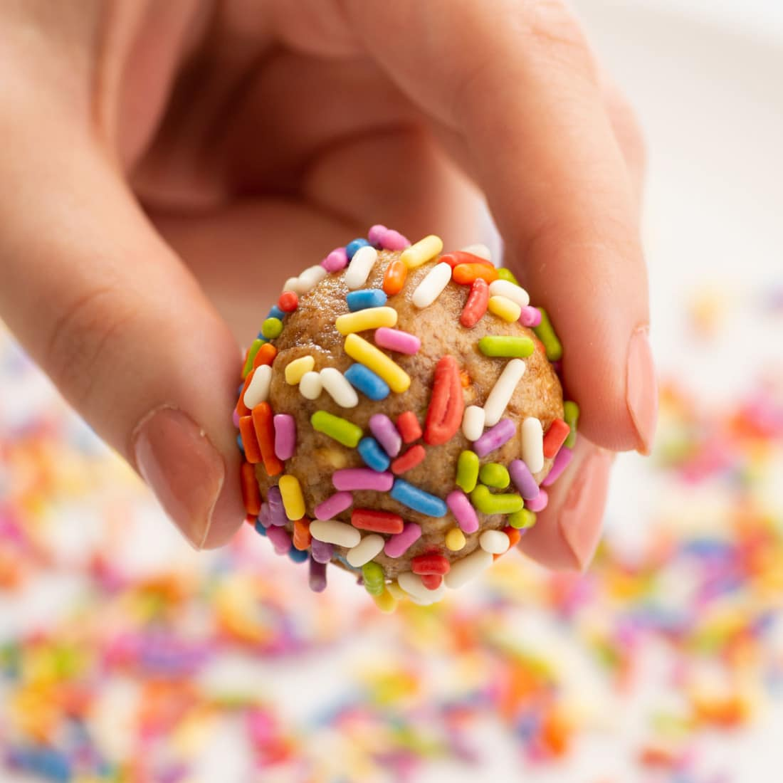 up close view of full birthday cake energy bite coated with sprinkles