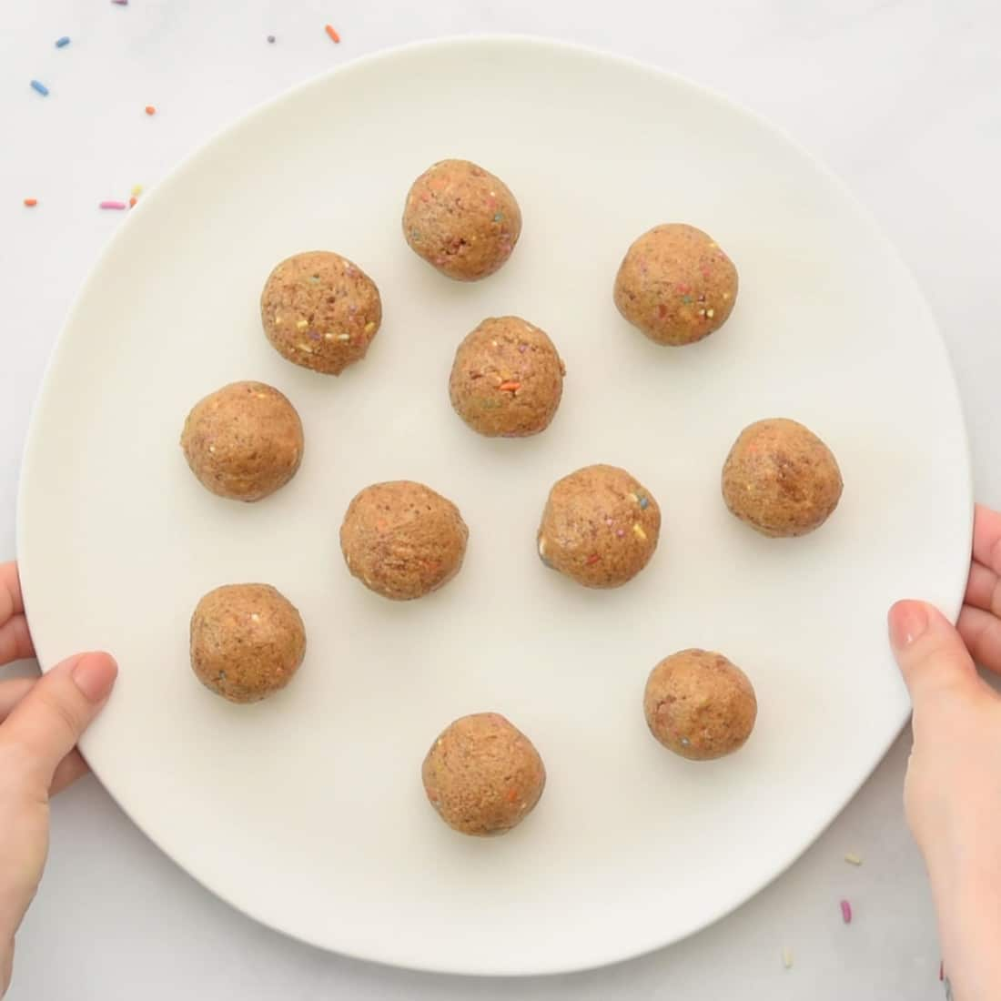 rolled balls with sprinkles on a plate