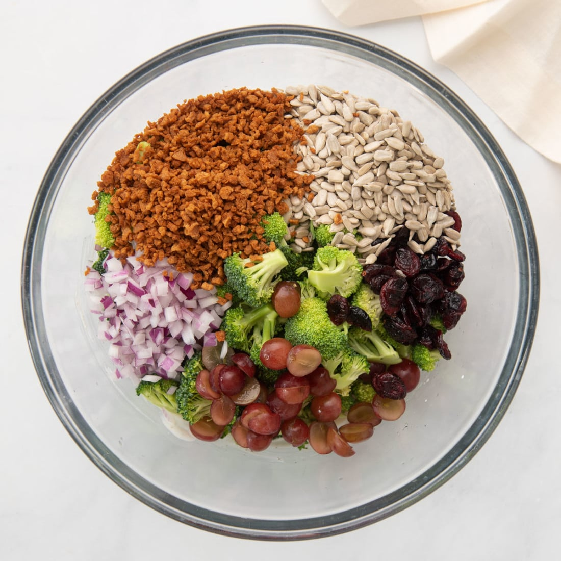 bowl with chopped florets, sunflower seeds, grapes, cranberries, and onion