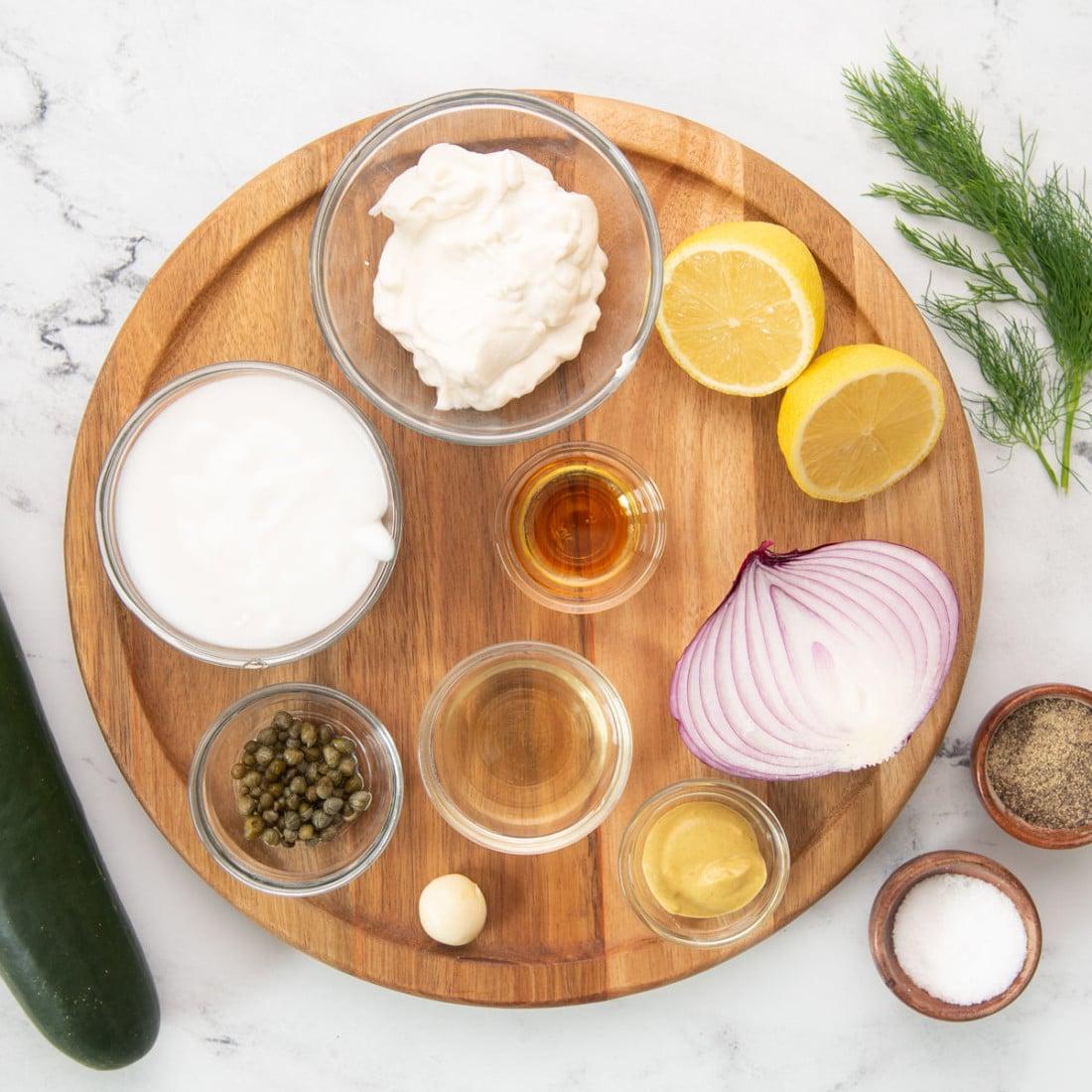 plant-based mayo, yogurt, vinegar, lemon, capers, onion, cucumber, dill on a board