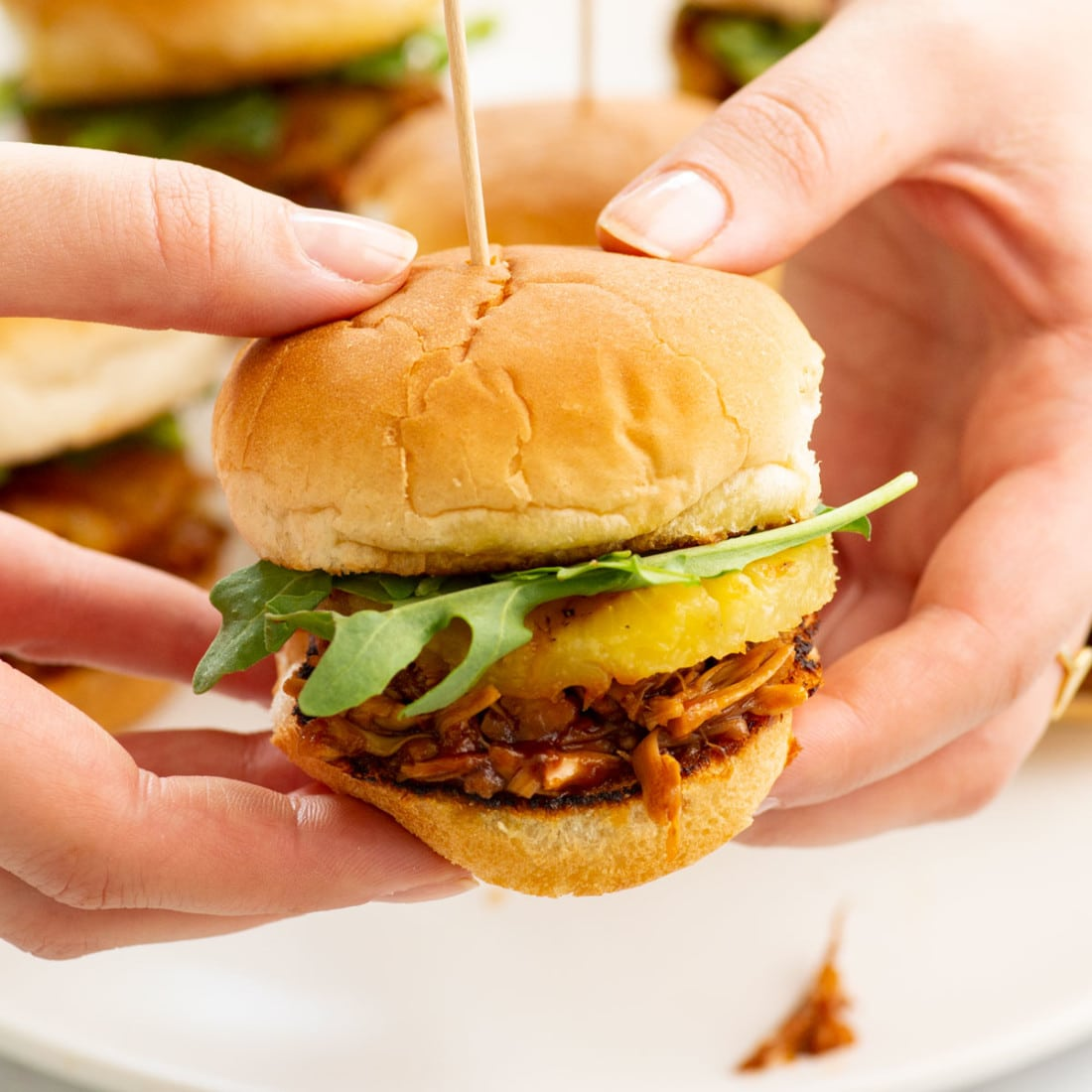 hands holding jackfruit sliders with pineapple and homemade sweet and tangy sauce