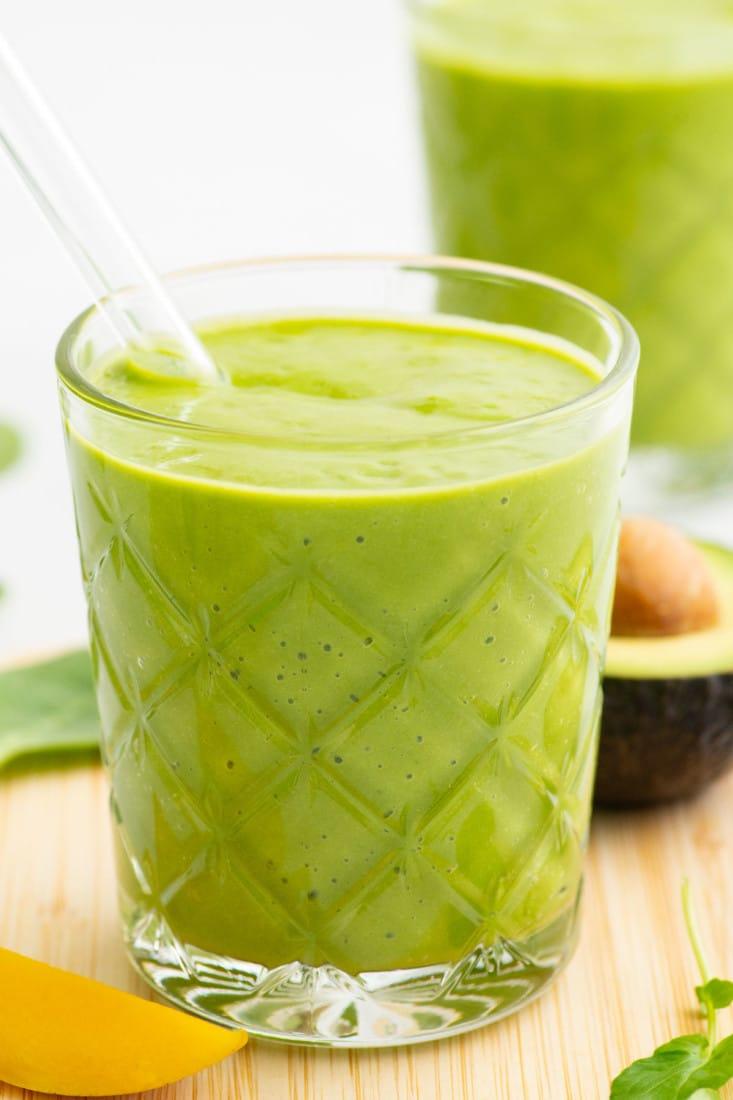 glass of vegan mango green smoothie with straw