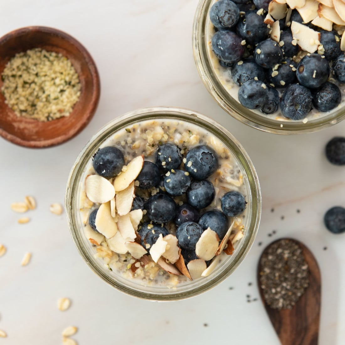 overhead view of vegan overnight oats loaded with fresh blueberries and almond slivers