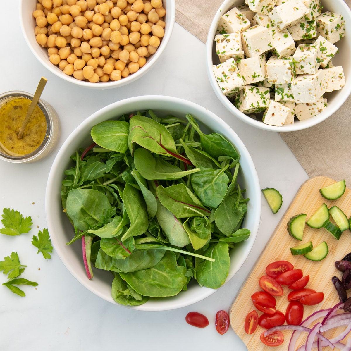 greens, sliced veggies, chickpeas, cubes of feta, salad dressing
