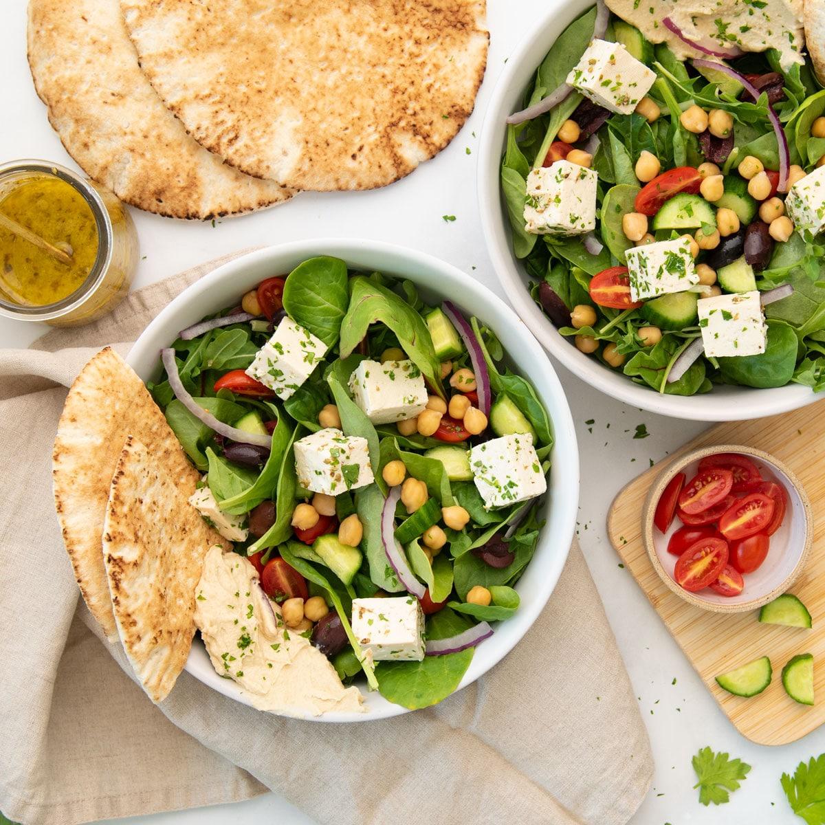 bowls of vegan greek salad loaded with veggies, feta, hummus, and slices of pita
