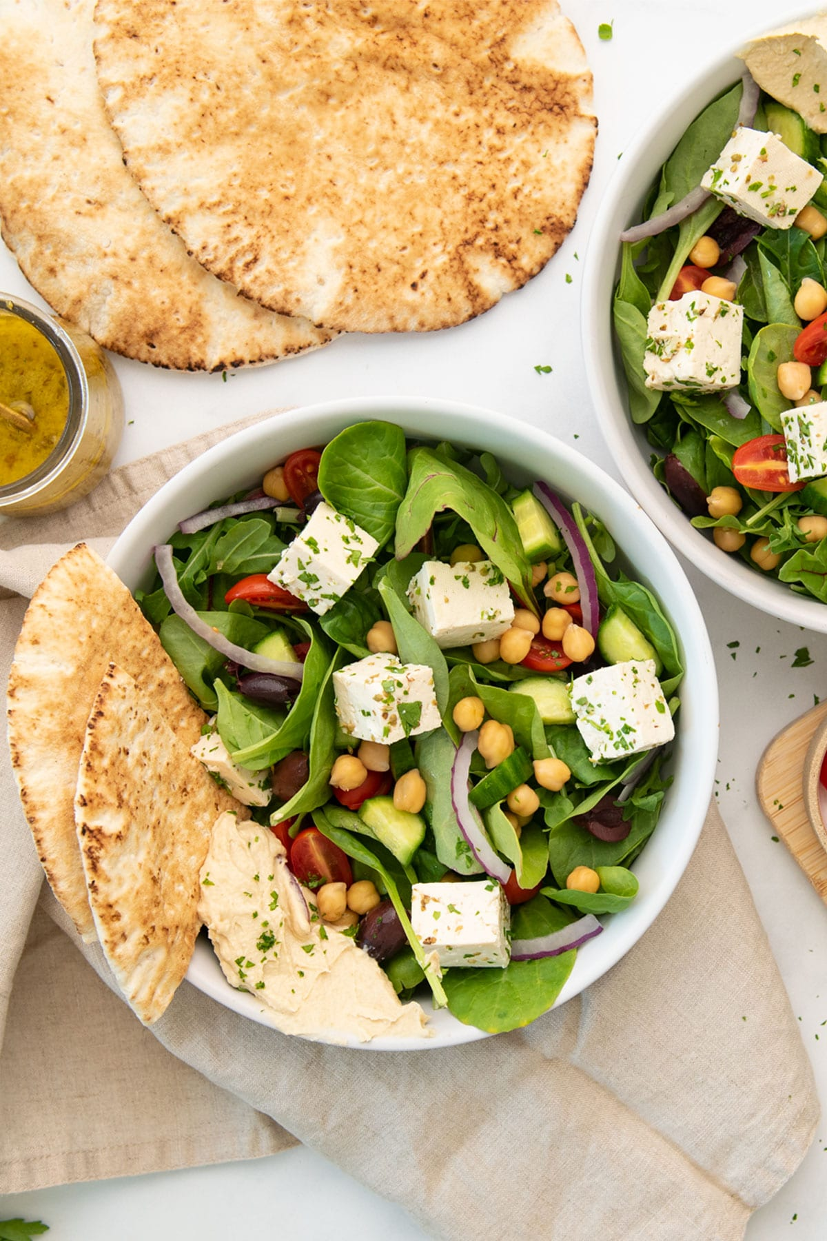 overhead view of two bowls with vegan Greek salad and pita bread slices