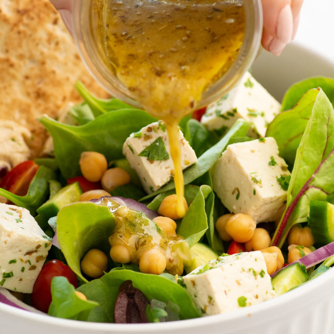 close up view of pouring Greek salad dressing over the bowl of salad