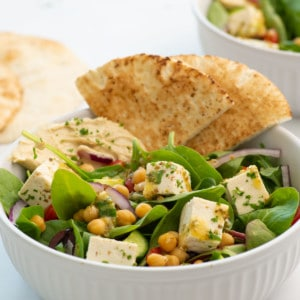 side view of vegan Greek salad in a bowl with pita