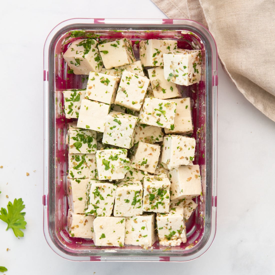 container with tofu feta cubes coated in Greek marinade