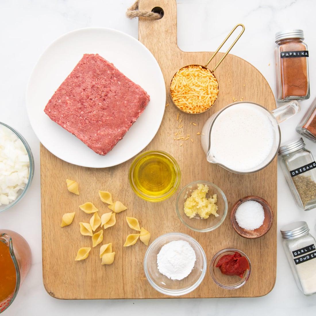 ingredients - impossible beef, cheese, oat milk, seasonings on a board