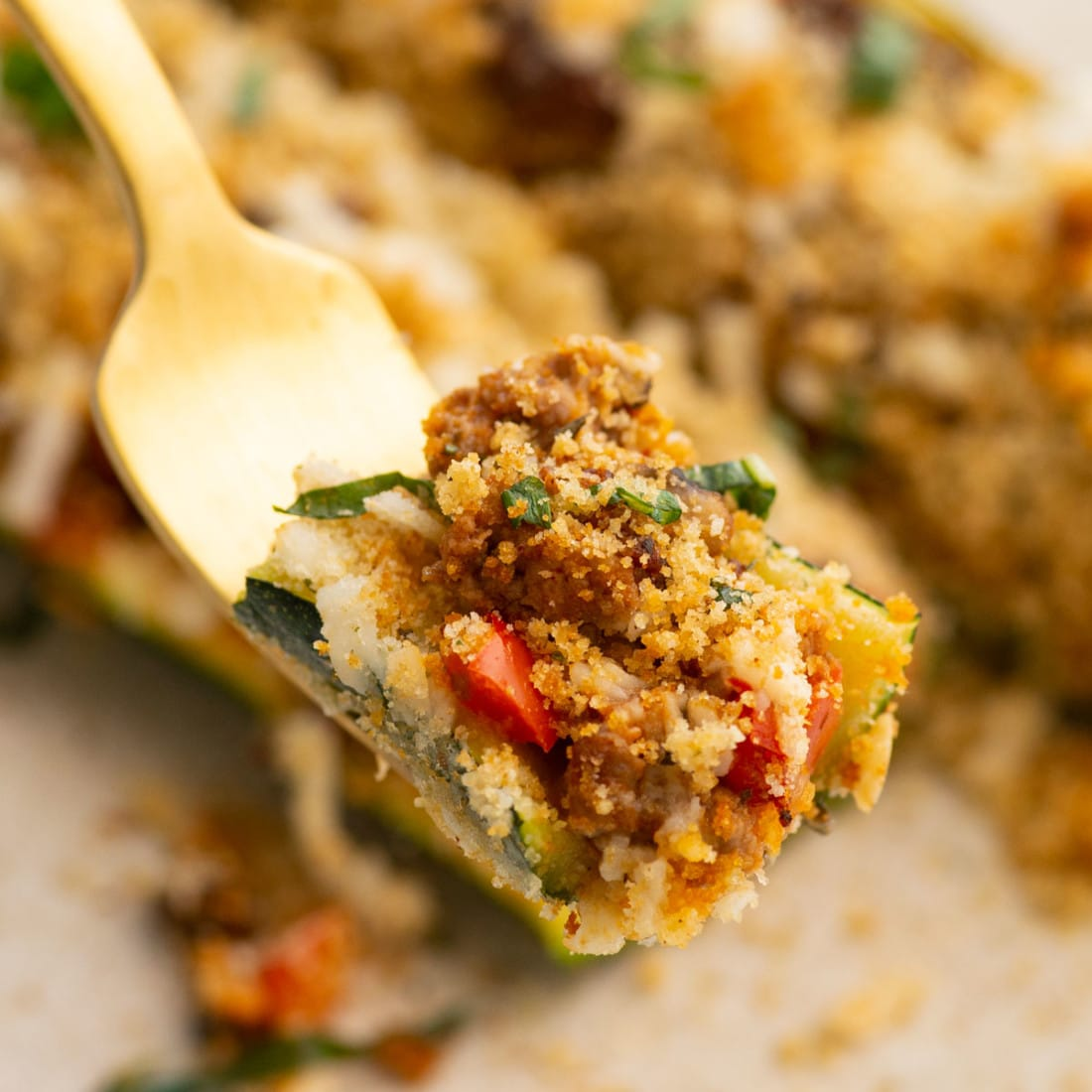 taking a bite of zucchini, meatless meat tomato sauce, veggies, plant-based cheese, and breadcrumbs