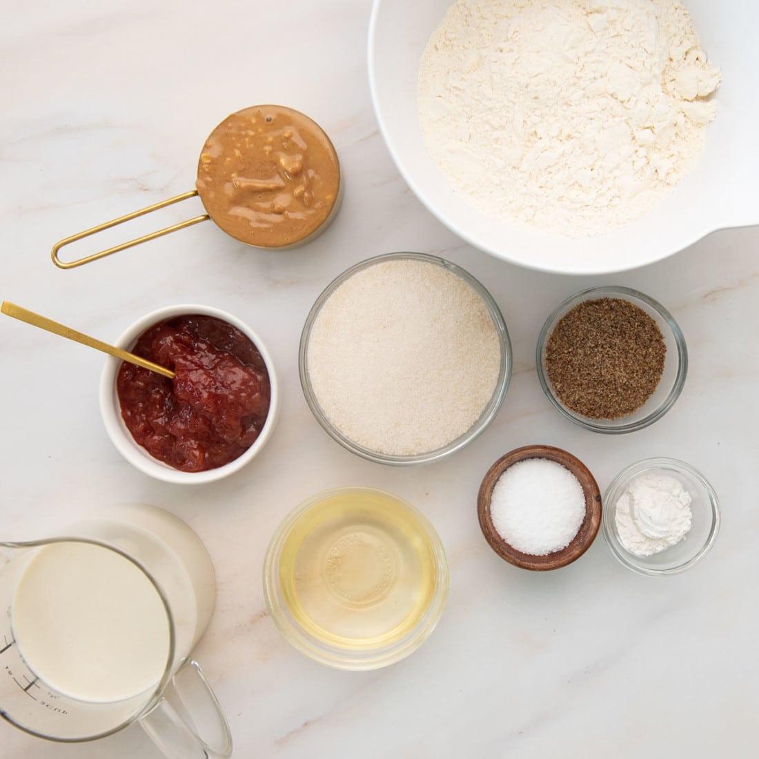 overhead view of ingredients: jam, pb, flax, flour, sugar, baking powder, oat milk