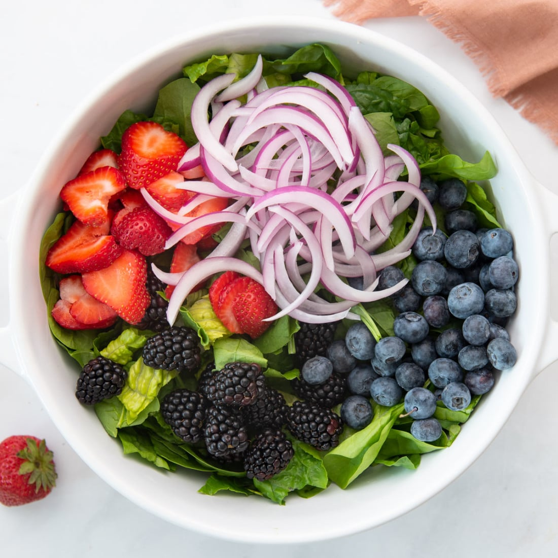 spinach, strawberries, blackberries, blueberries, red onion, and avocado in large salad bowl