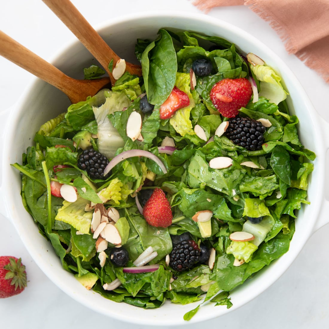 berry salad in large white bowl with wood salad spoons