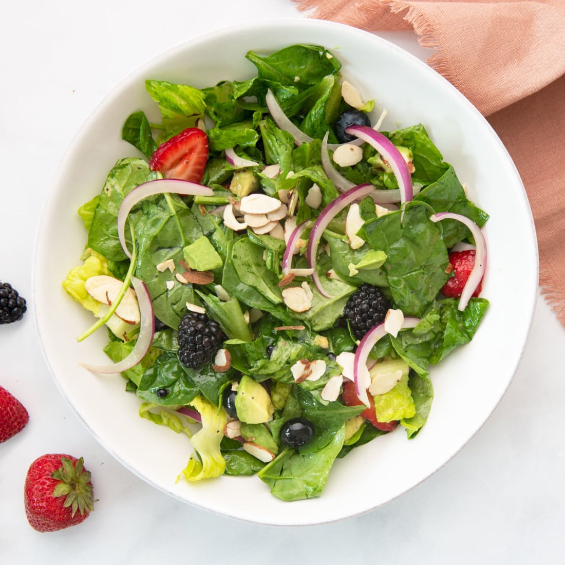 berry salad in white bowl with pink napkin