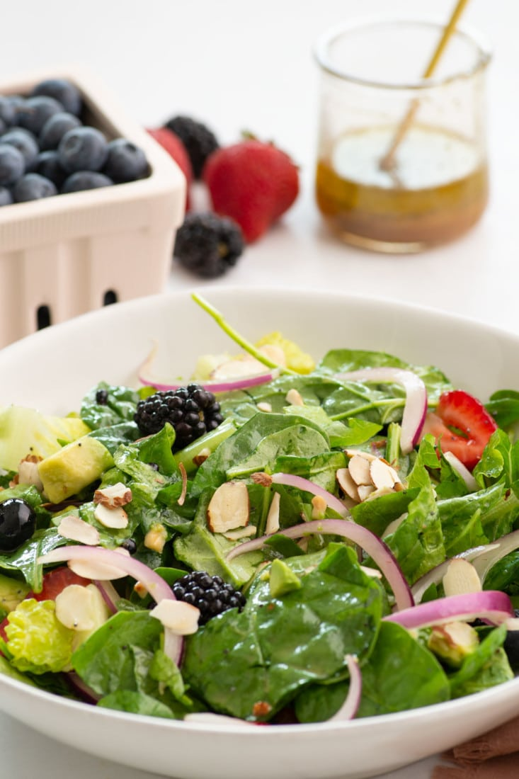 berry salad in white bowl with dressing in background