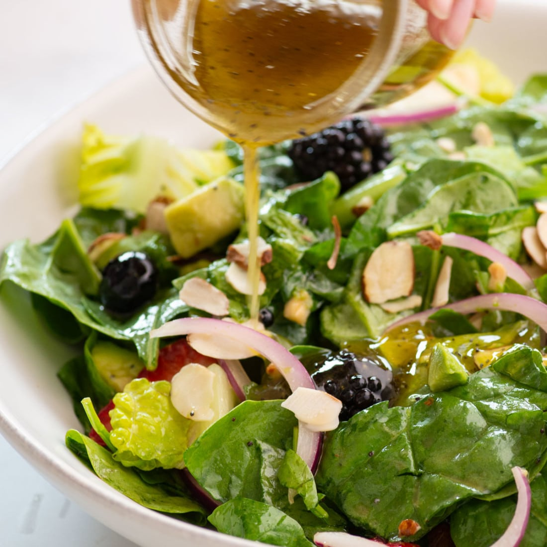 hand pouring dressing over salad in white bowl