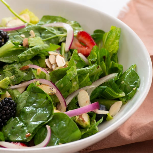 closeup of salad with spinach, red onions, berries, and almonds in white bowl